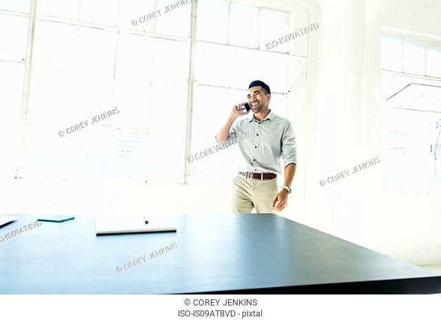 Businessman speaking on smartphone by office window