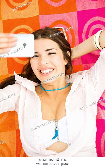 Portrait of young laughing woman lying on beach towel taking a selfie, elevated view