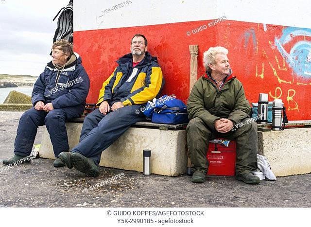 Scheveningen, Netherlands. Three mature adult and retired men sitting down at the harbor head light house, while fishing on the shoreline