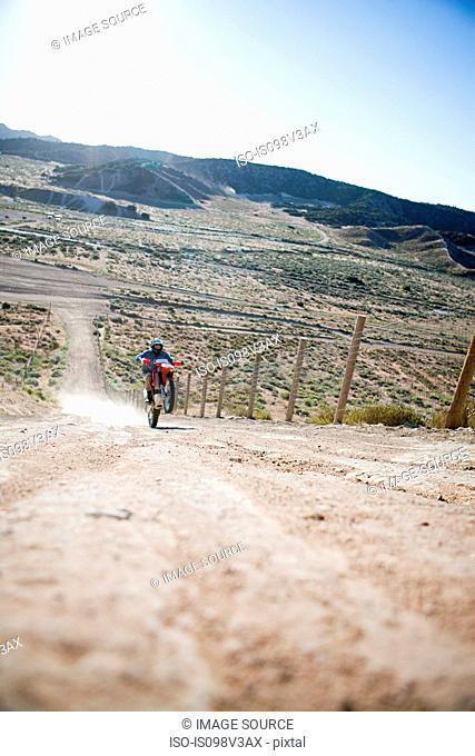 Man doing wheelie on dirt bike on dirt track