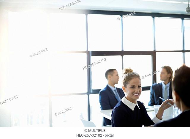 Smiling businesswoman talking in conference room meeting