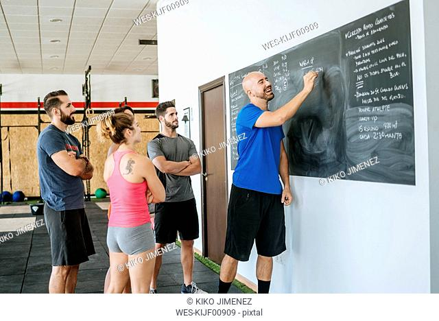 Coach in a fitness class writing on blackboard