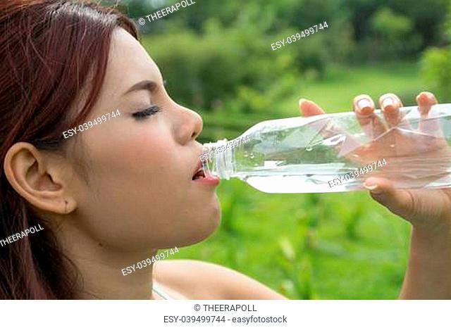 Closeup of a young woman drinking water at the park