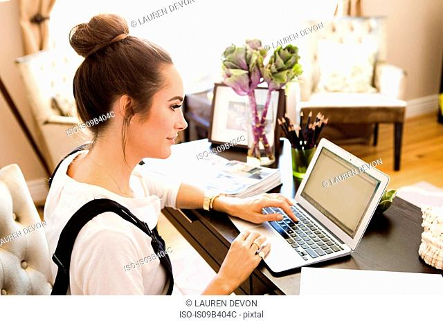 Female fashion and lifestyle blogger typing on laptop at desk