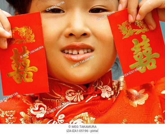 Portrait of a girl holding red gift packets Hong Bao near her face