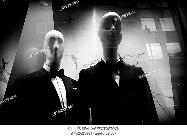 Two men mannequins in a shop window with reflections in the glass, dressed with bow tie and jacket. Savile Row, London, England, UK, Europe