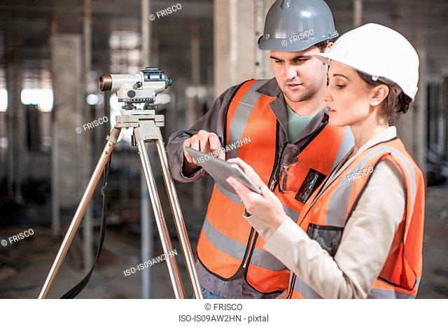 Female and male surveyor using digital tablet on construction site