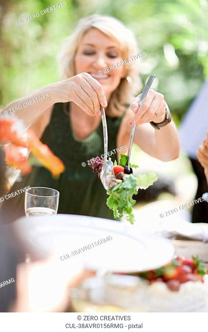 Woman serving salad outdoors