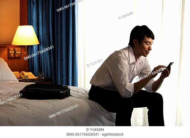 young man sitting on bed in hotel room texting on phone