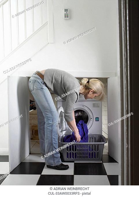 Woman unloading clothes from dryer