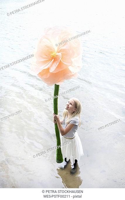 Smiling blond girl standing in a lake holding oversized artificial flower