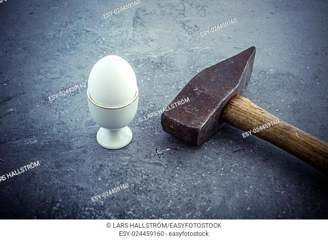 Egg and hammer on stone table. Symbol of strength, force and something hard and unbreakable. Concept of fragility and power