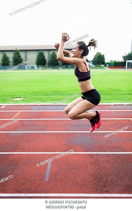 Teenage runner, jumping for joy on race track