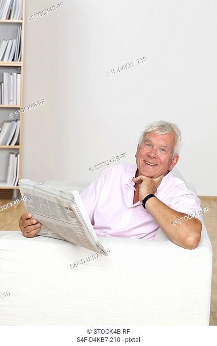 Senior man reading newspaper on couch