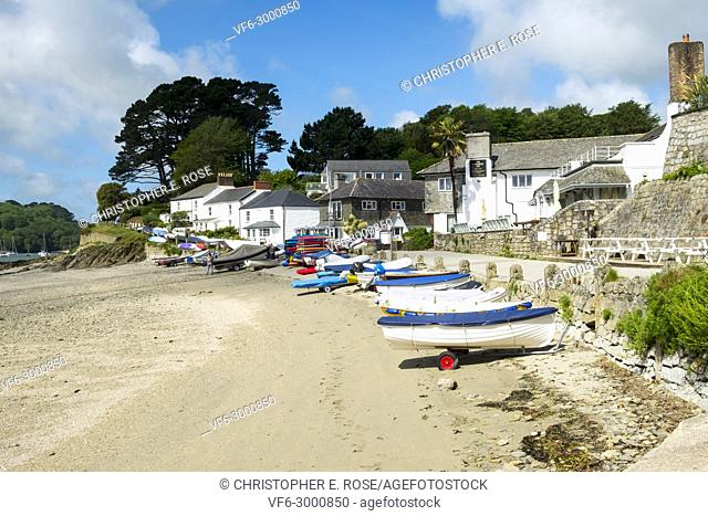 At low tide many colourful small boats wait at the top of the beach in the tourist attraction and boating centre of picturesque Helford Passage, Cornwall, UK