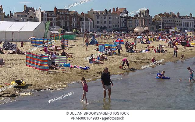Pan across Weymouth beach at the height of summer