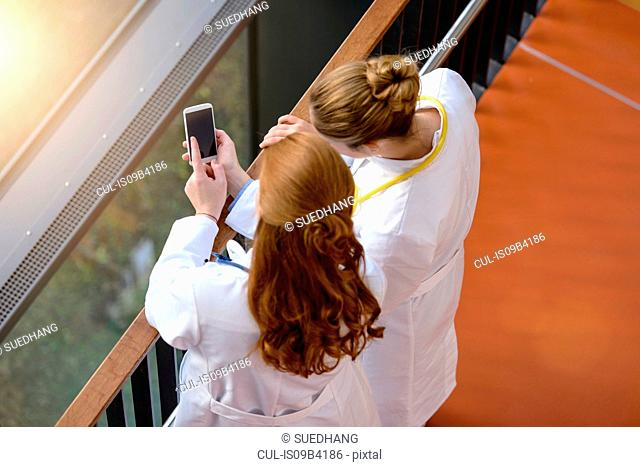 High angle view of two female doctors on hospital balcony using smartphone touchscreen