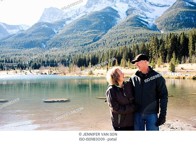 Senior couple standing beside river, Three Sisters, Rocky Mountains, Canmore, Alberta, Canada