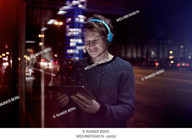 Germany, Munich, man with headphones standing at bus stop using digital tablet at night