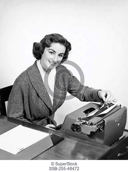 Portrait of a businesswoman typing on a typewriter in an office