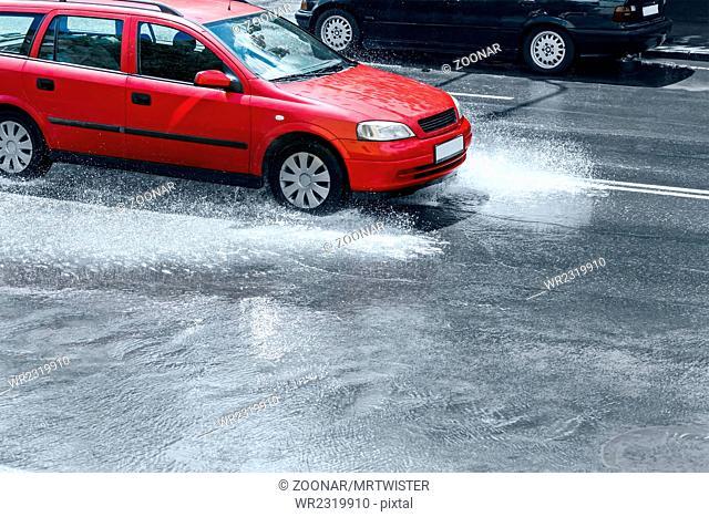 splashing red car on flooded street