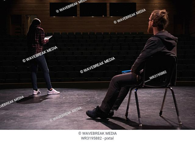 Female actress reading script while male actor looking at her on stage