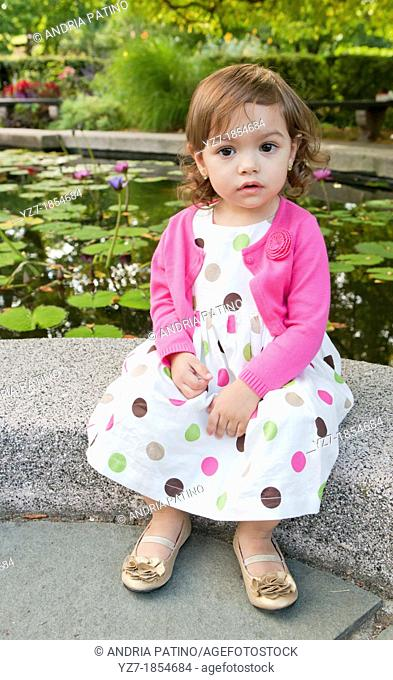 Toddler girl sitting looking into camera in garden
