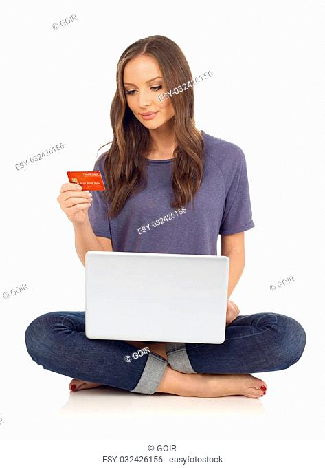 Teenager looking at a credit card and holding a laptop, white background