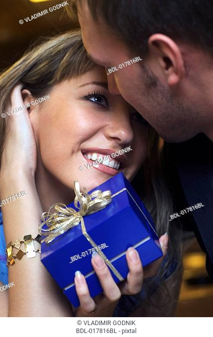 young couple exchanging gifts tenderly looking at each other