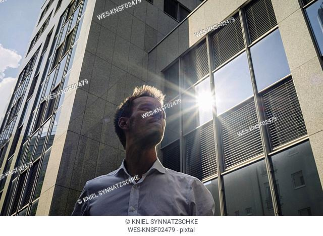 Businessman standing outdoors with sun reflecting in office building