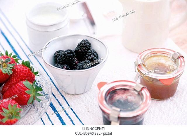 Summer fruits in bowls and preserves in jars on tablecloth