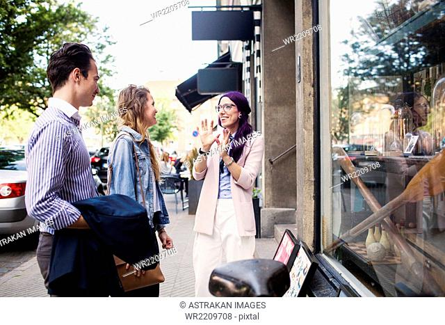Friends talking outside shop window
