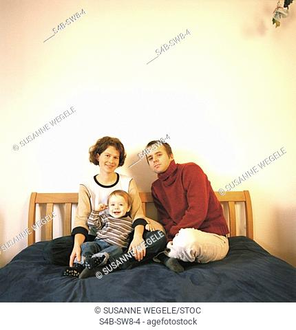 Young family sitting on bed