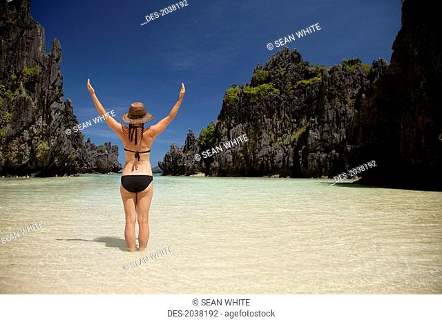A Woman Tourist Wearing A Sun Hat And Bikini Stands With Arms Raised In The Clear Waters Of Matinloc Island Near El Nido And Corong Corong, Bacuit Archipelago