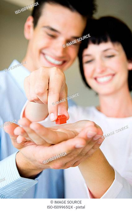 Couple holding model house