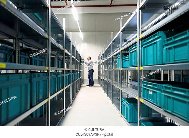 Worker taking box from shelf in factory