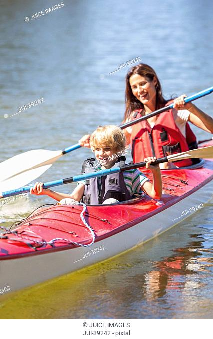 Happy mother and son in kayak on lake