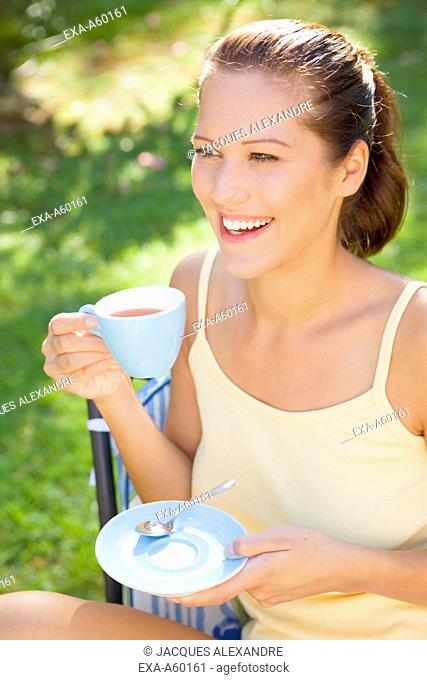 Cheerful attractive young woman holding cup
