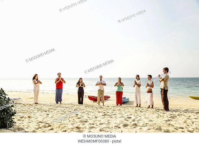 Thailand, Koh Phangan, group of people doing yoga on a beach