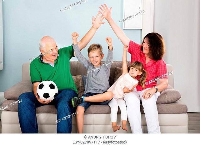 Family Of Soccer Fans Watching Football Match On Television With Kids