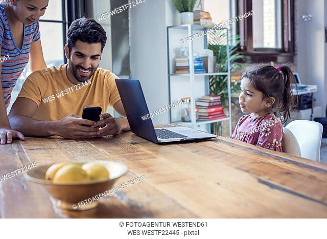 Family sitting in kitchen, parents using smart phone, daughter looking at laptop