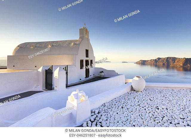 Small white church in Oia village on Santorini island, Greece.