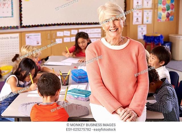 Senior teacher in classroom with elementary school kids