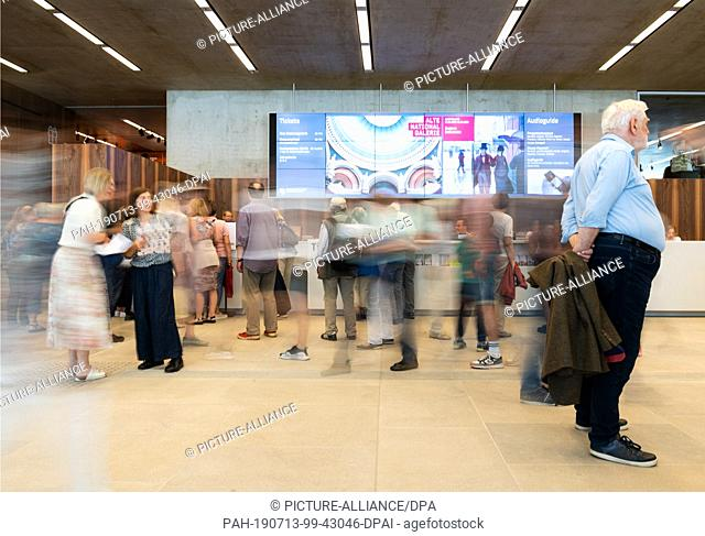 13 July 2019, Berlin: After the opening of the James Simon Gallery, visitors wait in front of the ticket counters or at the audio guides (motion blur due to...