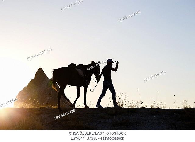 Man and horse silhouette in valley at Cappadocia,Anatolia,Turkey. Fairy tale chimneys in Cappadocia, tourist attraction places in Goreme, Cappadocia, Turkey