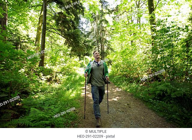 Man hiking with hiking poles on path in woods