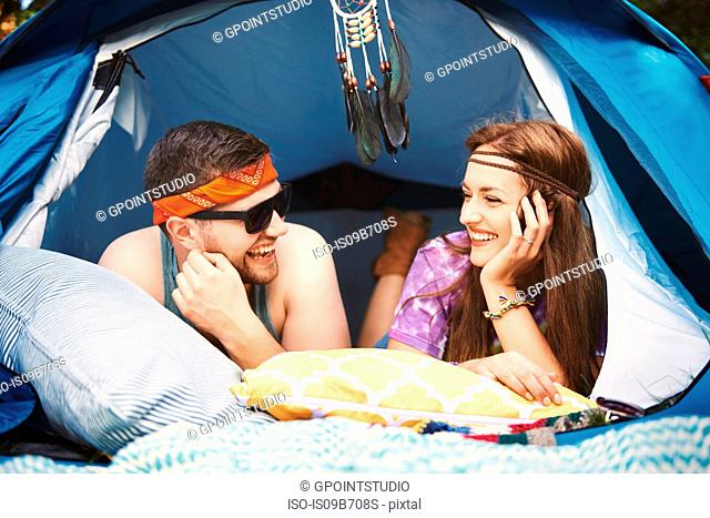 Young boho couple lying in tent at festival