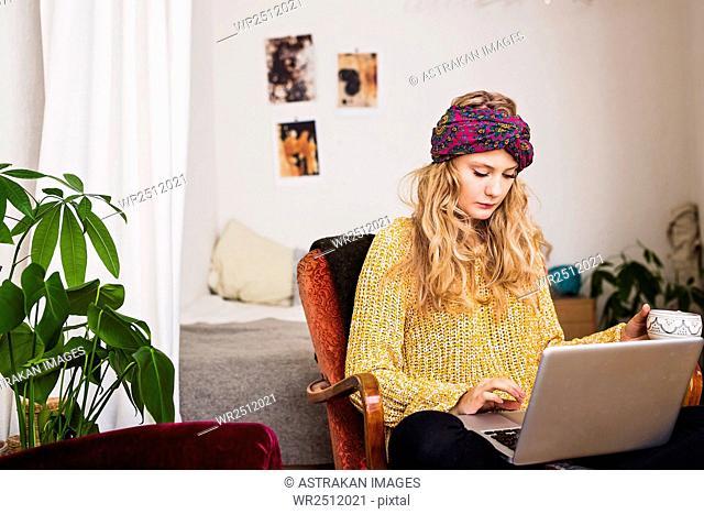 Woman wearing bandana using laptop while sitting at home
