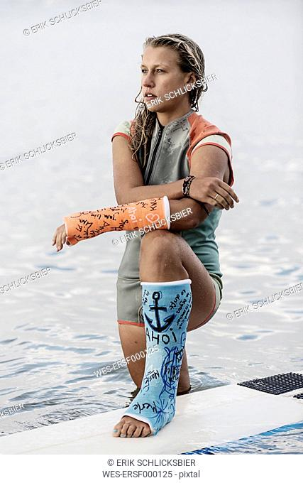 Portrait of female surfer with plastered arm and leg in plaster