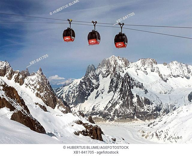 Small cable car Vallée Blanche from the mountain Aiguille du Midi, 3842m, at the Mont Blanc massif to Pointe Helbronner, 3462, behind the cabins, les Drus, 3754